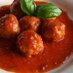 ITALIAN SAUSAGE MEATBALLS with tomato sauce and basil leaves